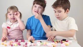 Drie kinderen eten suikergoed en zitten bij lijst stock videobeelden