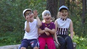 Drie kinderen glimlachen, omhelzen en trekken grimassen stock videobeelden