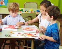 Drie kinderen het schilderen Stock Foto