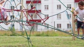 Drie kinderen kruipen in netto op speelplaats stock footage