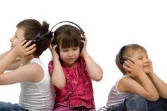 Drie Kinderen luisteren aan Muziek Stock Foto's