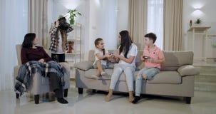 Drie kinderen met hun moeder en oma hebben een prettijd die samen op een virtuele werkelijkheidsglazen en een PSP zij spelen stock videobeelden