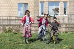 Drie kinderen op fietsen Portret van drie kleine fietsers die hun fietsen berijden Stock Afbeelding
