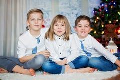 Drie kinderen, siblings, die hun Kerstmisportret hebben stock afbeelding