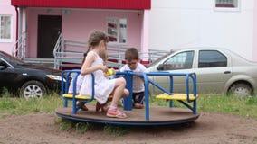 Drie kinderen spelen op carrousel op speelplaats stock videobeelden