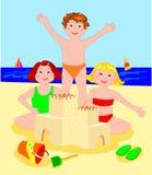 Drie kinderen terwijl het bouw van een kasteel van zand Stock Fotografie