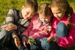 Drie kinderen zitten en tonen hun spinners royalty-vrije stock afbeeldingen