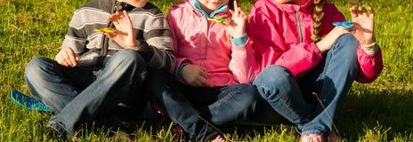 Drie kinderen zitten en verdraaien hun spinners en glimlach bij overwinning royalty-vrije stock fotografie
