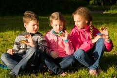 Drie kinderen zitten en verdraaien hun spinners en wachten op resultaten stock foto's