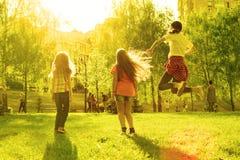 Drie kinderenmeisjes bij zonsondergang die in het park, achtermening springen stock foto