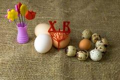 Drie kippeneieren en van kwartelseieren Parelhoenei ligt samen op een houten lijst Stock Fotografie