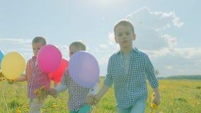 Drie kleine broers die met kleurenballons bij het bloeiende gebied op de zomervakantie lopen stock footage