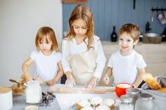 Drie kleine chef-koks die van in de keuken genieten die groot maakt knoeien Jonge geitjes die koekjes in de keuken maken royalty-vrije stock afbeelding