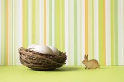 Drie kleine eieren in nest met houten pictogram van konijn Royalty-vrije Stock Afbeeldingen