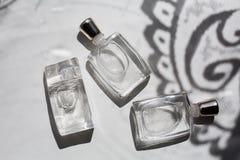 Drie kleine flessen parfum in grijs stock foto's