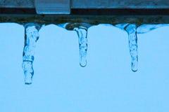 Drie kleine ijskegels die van het dak tegen een blauwe hemel bij schemer hangen stock foto