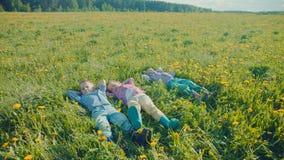 Drie kleine jongens liggen op het gras en bekijken de wolken in de hemel na het spel stock video