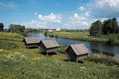 Drie kleine oude blokhuizen op hoge stelten door de rivier stock foto