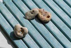 Drie kleine seastones liggen op een houten blauwe achtergrond stock foto