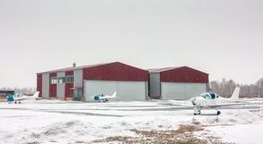 Drie kleine sportenvliegtuigen naast hangaars bij het de wintervliegveld Stock Afbeelding