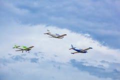 Drie kleine vliegtuigen die in de hemel tegen een achtergrond van wolken vliegen Stock Fotografie