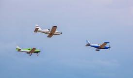 Drie kleine vliegtuigen die in de hemel tegen een achtergrond van wolken vliegen Stock Afbeelding