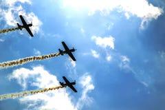 Drie kleine vliegtuigen die in de hemel tegen een achtergrond van wolken vliegen Stock Foto