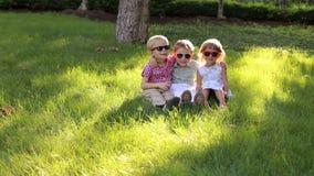 Drie kleine vrolijke kinderen in zonnebril zitten op het gras in het Park stock footage