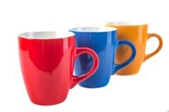 Drie kleuren ceramische koppen op een witte achtergrond Stock Foto's