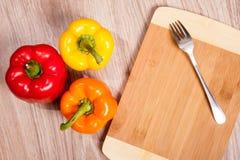 Drie kleuren de peper op houten scherpe achtergrond met vork Gele, oranje en Spaanse pepers Royalty-vrije Stock Afbeeldingen