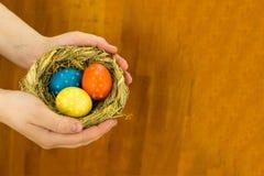 Drie kleurrijk eieren geeloranje blauw met bloemenpatroon in een kaart van de het ontwerpgroet van Pasen van het stronest met exe stock foto