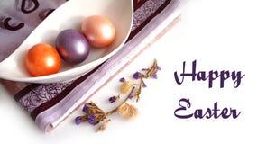 Drie kleurrijke eieren in een kom, een purpere handdoek stock afbeeldingen