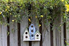 Drie kleurrijke vogelhuizen op oude omheining met gele bloemen royalty-vrije stock afbeeldingen