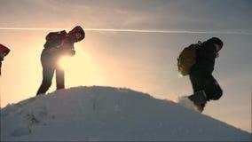 drie klimmers beklimmen achter elkaar op een snow-covered heuvel het team van bedrijfsmensen gaat naar overwinning en succes stock footage