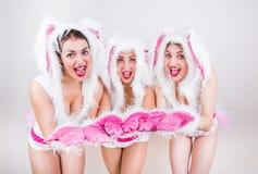 Drie knappe meisjes in konijnkostuum voelen gelukkig vooruit zettend hun handen Stock Fotografie