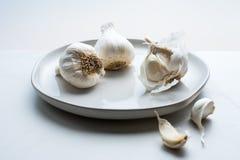 Drie knoflookbollen op een witte plaat stock fotografie