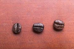 Drie Koffiebonen gezet op hout, de achtergrond van het kunstwerk Royalty-vrije Stock Afbeeldingen