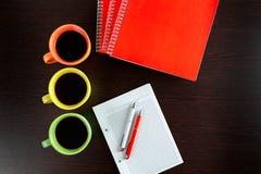 Drie koffiekoppen blijven op donkere bruine houten lijst zoals lichten naast sketchbook met oranje notitieboekjes en oranje en wi Stock Foto