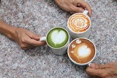 Drie kop van verschillende koffie wat cappucino, mocha latte en de holding van de karamelmelk met de hand van vriend op de rustie royalty-vrije stock foto's