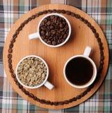 Drie koppen met verschillende stadia van koffie: groene en geroosterde bonen en espresso Op houten raad Op plaidtextuur Royalty-vrije Stock Fotografie