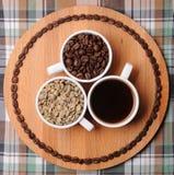 Drie koppen met verschillende stadia van koffie: groene en geroosterde bonen en espresso Op houten raad Op plaidtextuur Royalty-vrije Stock Afbeelding