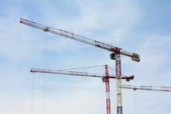 Drie krachtige bouwkranen tegen de hemel, terwijl het werken bouw stock afbeeldingen