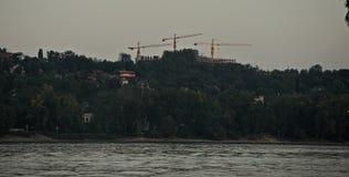Drie kranen op overkant van rivier Donau stock afbeelding