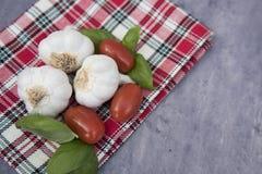 Drie kruidnagels van knoflook met basilicum en tomaten Stock Afbeelding