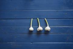 Drie kruidnagels van knoflook op blauwe houten lijst Royalty-vrije Stock Foto's