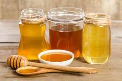 Drie kruiken, de kom, de lepel met een honing Royalty-vrije Stock Afbeeldingen