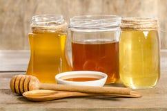Drie kruiken, de kom, de lepel met een honing Stock Foto's