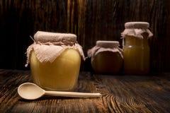 Drie kruiken honing op een houten achtergrond Royalty-vrije Stock Foto's