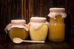 Drie kruiken honing op een houten achtergrond Stock Afbeelding