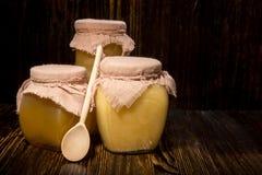 Drie kruiken honing op een houten achtergrond Stock Afbeeldingen